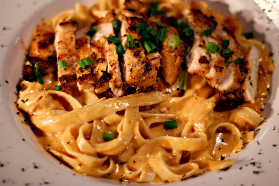 ... in a rich creamy sauce over angel hair pasta topped with chicken